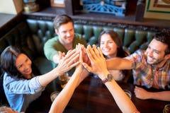 Amis buvant de la bière et faisant la haute cinq à la barre Photographie stock