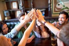 Amis buvant de la bière et faisant la haute cinq à la barre Photos stock