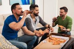 Amis buvant de la bière et mangeant de la pizza Images stock