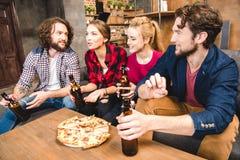 Amis buvant de la bière et mangeant de la pizza Photos libres de droits
