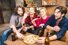Amis buvant de la bière et mangeant de la pizza Photos stock