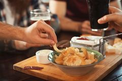 Amis buvant de la bière et mangeant des casse-croûte à la table Image stock
