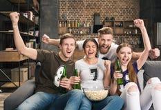 Amis buvant de la bière et mangeant du maïs éclaté Images stock