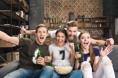 Amis buvant de la bière et mangeant du maïs éclaté Image stock