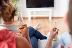Amis buvant de la bière et regardant la TV à la maison Photos libres de droits