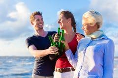 Amis buvant de la bière mis en bouteille à la plage Image libre de droits