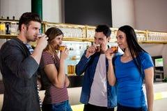 Amis buvant de la bière par le compteur de barre Photo libre de droits