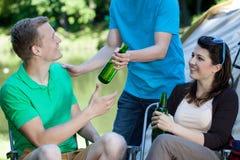Amis buvant de la bière par le lac Photographie stock