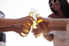 Amis buvant de la bière sur la plage Image libre de droits