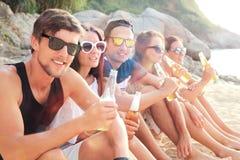 Amis buvant de la bière sur la plage Photographie stock