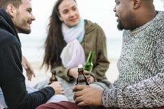 Amis buvant de la bière sur la plage Image stock