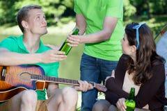 Amis buvant de la bière sur un camping Photo stock