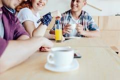 Amis buvant des boissons et parlant en café Image libre de droits