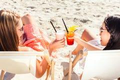 Amis buvant des cocktails dans la barre de plage Photographie stock