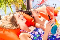 Amis buvant des cocktails dans la barre de plage Photo libre de droits