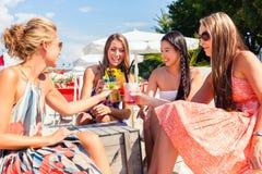 Amis buvant des cocktails dans la barre de plage Images stock