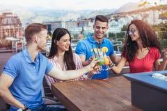 Amis buvant des cocktails extérieurs sur un balcon d'appartement terrasse Images stock