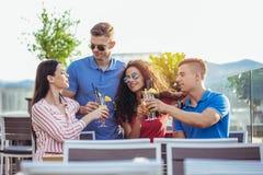 Amis buvant des cocktails extérieurs sur un balcon d'appartement terrasse Photo libre de droits
