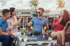 Amis buvant des cocktails extérieurs sur un balcon d'appartement terrasse Photo stock
