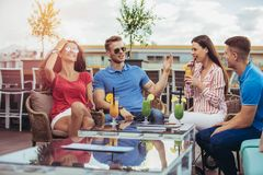 Amis buvant des cocktails extérieurs sur un balcon d'appartement terrasse Image libre de droits