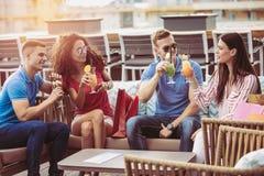 Amis buvant des cocktails extérieurs sur un balcon d'appartement terrasse Photographie stock