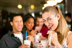 Amis buvant des laits de poule dans un bar Photographie stock libre de droits