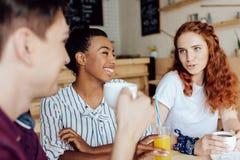 Amis buvant du café et du jus Photo libre de droits