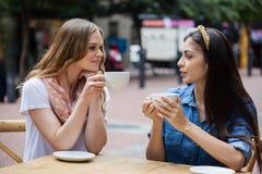 Amis buvant du café tout en se reposant au café de trottoir Photographie stock libre de droits