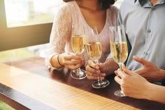 Amis buvant du champagne Images libres de droits