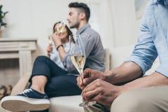 Amis buvant du champagne des verres tout en se reposant sur le sofa Images stock
