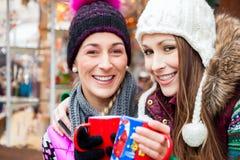 Amis buvant du lait de poule sur le marché de Noël Photos stock