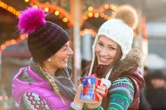 Amis buvant du lait de poule sur le marché de Noël Images stock