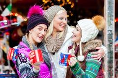Amis buvant du lait de poule sur le marché de Noël Photographie stock libre de droits
