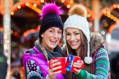 Amis buvant du lait de poule sur le marché de Noël Image stock