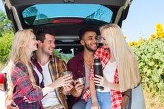 Amis buvant du thé tenant le thermos de tasses de café se reposant dans la campagne extérieure de tronc de voiture Image libre de droits