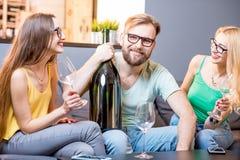 Amis buvant du vin à la maison Image libre de droits