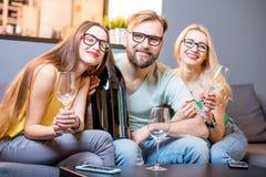 Amis buvant du vin à la maison Photographie stock
