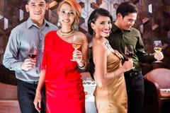 Amis buvant du vin dans la barre de fantaisie Photographie stock libre de droits