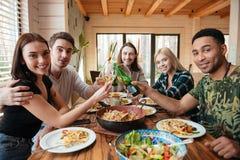 Amis buvant du vin et faisant tinter des verres sur la cuisine Photographie stock