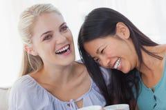 Amis buvant le café ensemble et rire Image stock