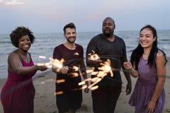 Amis célébrant avec des cierges magiques à la plage Photos libres de droits