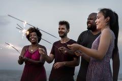 Amis célébrant avec des cierges magiques à la plage Photo stock