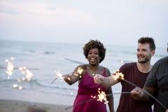 Amis célébrant avec des cierges magiques à la plage Image stock