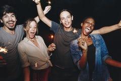 Amis célébrant avec des cierges magiques pendant la nuit Photographie stock