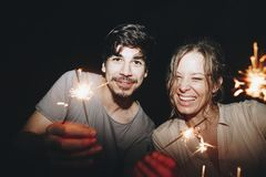 Amis célébrant avec des cierges magiques pendant la nuit Image stock