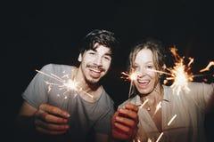 Amis célébrant avec des cierges magiques pendant la nuit Photos stock