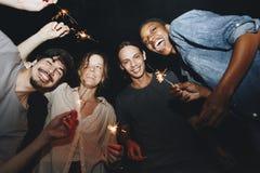 Amis célébrant avec des cierges magiques pendant la nuit Photos libres de droits