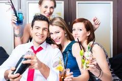 Amis célébrant avec le barkeeper dans la barre de cocktail Image stock