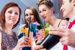 Amis célébrant avec le barkeeper dans la barre de cocktail Image libre de droits