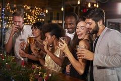 Amis célébrant ensemble à une fête de Noël dans une barre Images stock